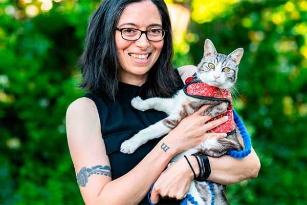 smiling woman holding her cat that is wearing a red vest